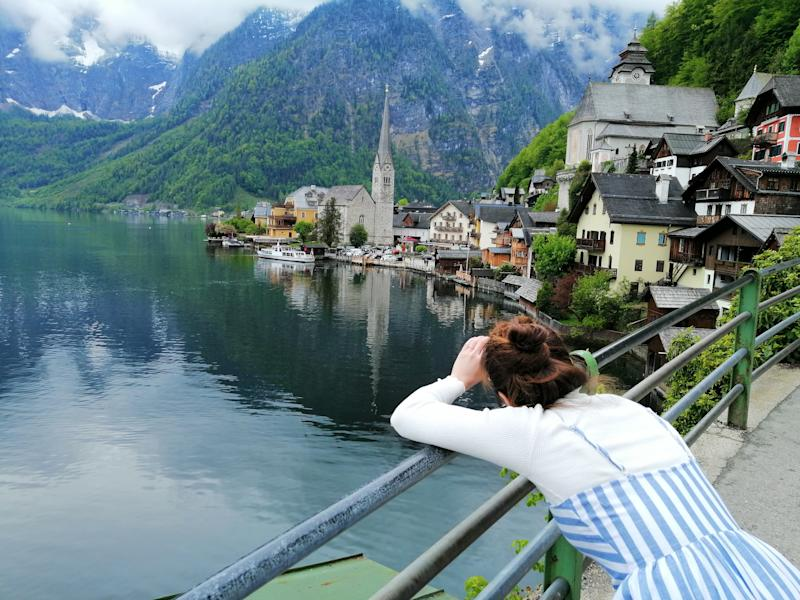 "16 May 2019, Austria, Hallstatt: A tourist photographs Lake Hallstatt. The World Heritage Community, with only 780 citizens, is visited by more than one million tourists a year. From 2020, the municipality wants to drastically reduce the number of coaches by selling access permits. (to dpa-Korr ""Fight the Bus Collapse"") Photo: Matthias Röder/dpa (Photo by Matthias Röder/picture alliance via Getty Images)"