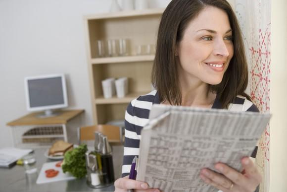 A smiling woman holding a financial newspaper while staring off into the distance.
