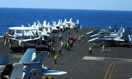 Carrier air crew converge at the flight deck of USS Theodore Roosevelt to guide operating aircraft while transiting the South China Sea April 10, 2018. REUTERS/Karen Lema
