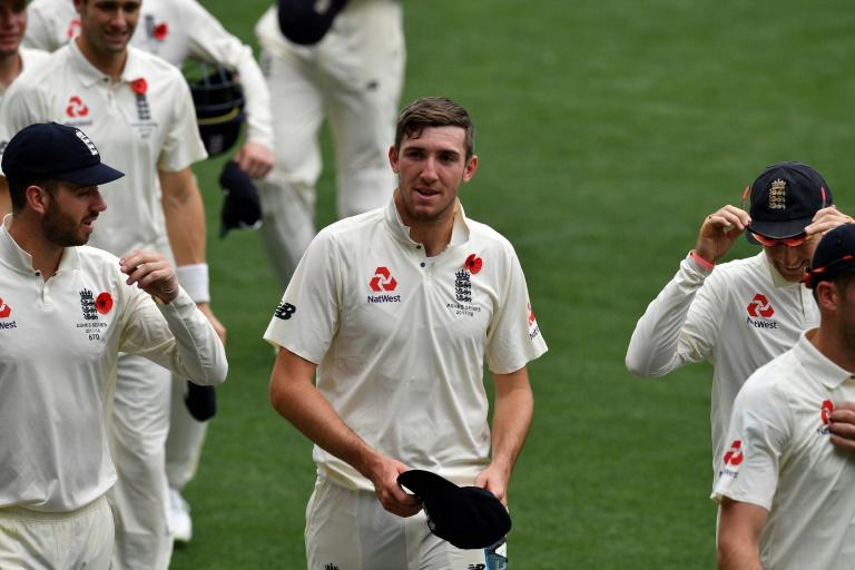 England's paceman Craig Overton (C) walks off the field with teammates following their victory against Cricket Australia XI on the last day of a four-day Ashes tour, at Adelaide Oval, on November 11, 2017
