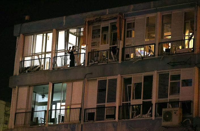 A person stands on the balcony of a building with a damaged facade