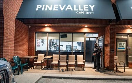 A police officer stands in the doorway of the Pine Valley Cafe Sport on Rowntree Dairy Road in Vaughan, one of 11 cafes where police executed warrants in an illegal gaming investigation named Project Sindacato in Vaughan