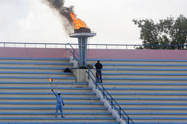 A ceremonial torch is lit to mark the reopening of the stadium in Mogadishu, Somalia Tuesday, June 30, 2020. At least three mortar blasts struck the Mogadishu Stadium Tuesday evening, just hours after it was reopened by Somalia's President Mohamed Abdullahi Mohamed, who had left before the shells hit, following years of instability. (AP Photo/Farah Abdi Warsameh)