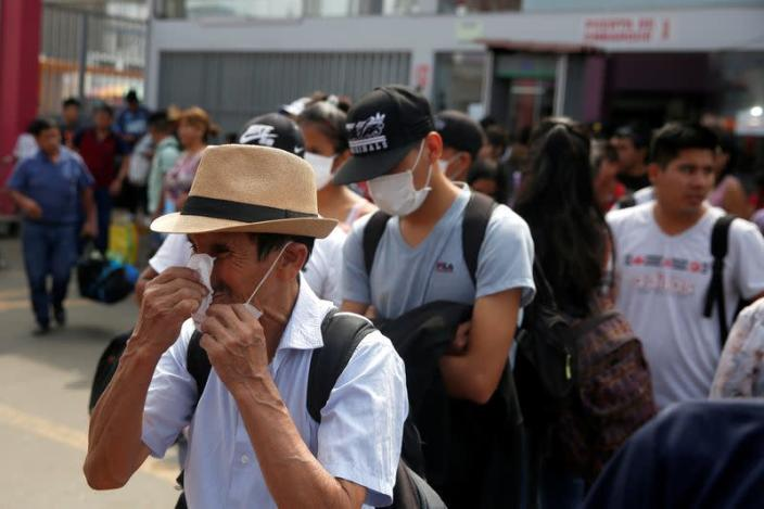 A man wipes his nose while waiting to board a bus at a bus station after Peru's government deployed military personnel to block major roads, as the country rolled out a 15-day state of emergency to slow the spread of coronavirus disease (COVID-19), in Lima