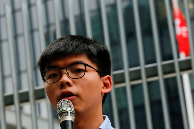 FILE PHOTO - Pro-democracy activist Joshua Wong speaks to journalists after being disqualified from running in the local district's council elections in November, in Hong Kong