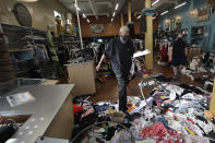 Terrel Ransom, center, store manager for Buffalo Exchange walks over clothes in the damaged store, Sunday, May 31, 2020, in Los Angeles, following a night of unrest and protests over the death of George Floyd, a black man who was in police custody in Minneapolis. Floyd died after being restrained by Minneapolis police officers on May 25. (AP Photo/Marcio Jose Sanchez)