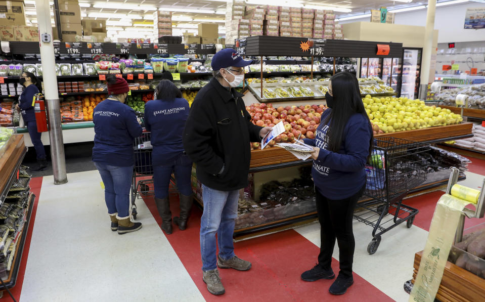 Alberto Raygoza, left, talks with Saint Anthony Hospital outreach worker Patricia Palato at a Chicago grocery store on Wednesday, Feb. 17, 2021. She approached Raygoza as he shopped for produce and made a vaccination appointment for him. In a race to boost vaccination rates as COVID-19 variants spread, U.S. communities are working to overcome mistrust and improve access among people of color. (AP Photo/Teresa Crawford)