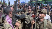 "This image made from undated video released by the state-owned Ethiopian News Agency on Monday, Nov. 16, 2020 shows Ethiopian military cheering and dancing in front of cameras on a road in an area near the border of the Tigray and Amhara regions of Ethiopia. Ethiopia's prime minister Abiy Ahmed said in a social media post on Tuesday, Nov. 17, 2020 that ""the final and crucial"" military operation will launch in the coming days against the government of the country's rebellious northern Tigray region. (Ethiopian News Agency via AP)"
