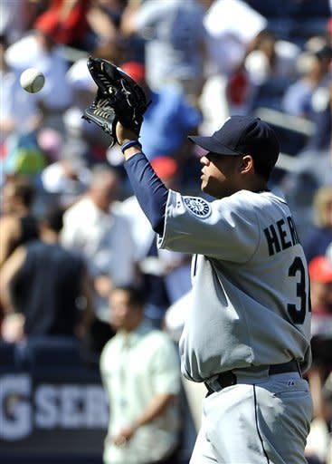 Seattle Mariners starting pitcher Felix Hernandez tosses the ball after the Mariners' 1-0 win over the New York Yankees in a baseball game Saturday, Aug. 4, 2012, at Yankee Stadium in New York. (AP Photo/Kathy Kmonicek)