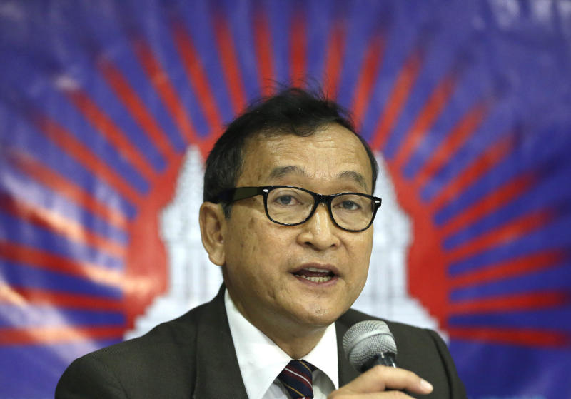 FILE - In this Sept. 10, 2012 file photo, Cambodian opposition leader Sam Rainsy, who is currently living in exile in France, talks about the opposition's plans for next year's elections in Cambodia during the launching of the International Parliamentary Committee for Democratic Elections in Cambodia with Philippine Sen. Franklin Drilon in San Juan, east of Manila, Philippines. Cambodia's charismatic self-exiled opposition leader vowed to return to Cambodia ahead of this month's general election to help challenge the 28-year rule of Prime Minister Hun Sen. The Cambodian government said Rainsy is welcome home but could face arrest if he returns. (AP Photo/Bullit Marquez)