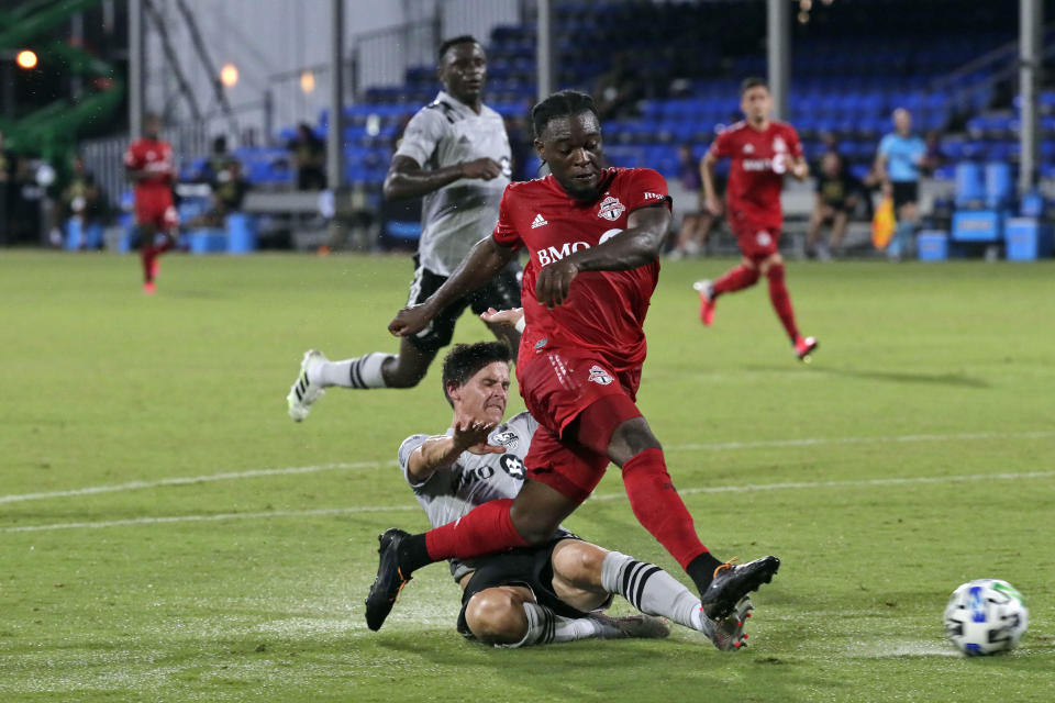 FILE - Toronto FC forward Ayo Akinola, front, scores his second goal of the game during the first half of an MLS soccer match against the Montreal Impact in Kissimmee, Fla., in this Thursday, July 16, 2020, file photo. Akinola is being talked about as a potential breakout star for the upcoming Major League Soccer season. (AP Photo/John Raoux, File)