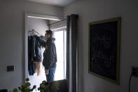 Comedian Brad Pierce, right, hangs up his jacket at his home in West Warwick, R.I., Friday, Jan. 8, 2021. Pierce was finally doing well with his comedy when the pandemic hit. Now he wonders if he can possibly build up his career again. He has a friend who drives for Amazon and fears having to get a job like that while talking about the good old days when he was an entertainer. (AP Photo/David Goldman)