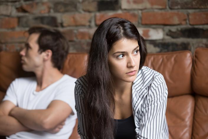 Angry unhappy young couple ignoring not looking at each other after family fight or quarrel, upset thoughtful spouses avoiding talk, sitting silently on couch, having relationship troubles.
