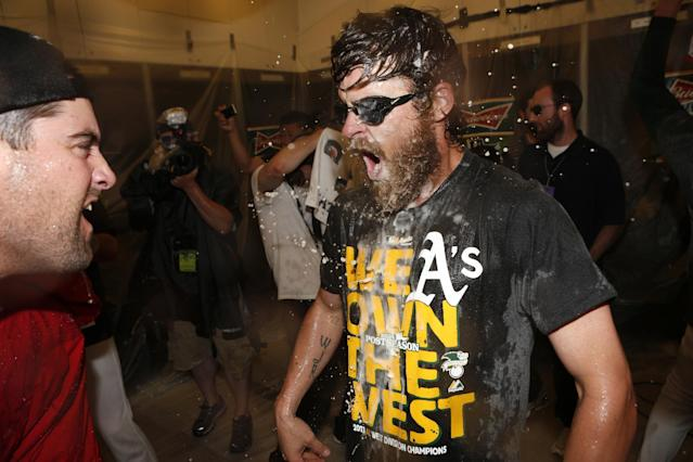 Oakland Athletics's Josh Reddick is doused by teammates after defeating the Minnesota Twins in a baseball game to become American League West champions on Sunday, Sept. 22, 2013, in Oakland, Calif. (AP Photo/Beck Diefenbach)
