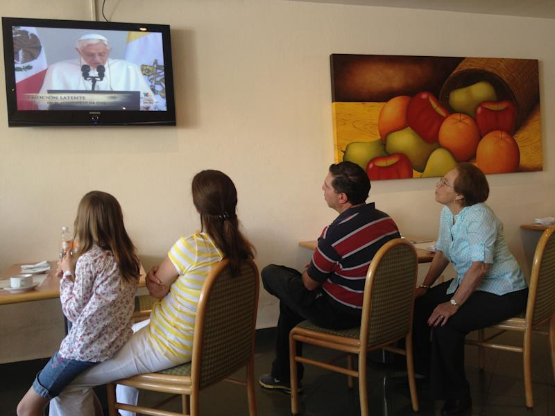 People watch a monitor at a hotel showing live coverage of a speech by Pope Benedict XVI at the airport prior to his departure in Leon, Mexico, Monday March 26, 2012. Pope Benedict XVI is departing Mexico and traveling to Cuba on Monday. (AP Photo/Dario Lopez-Mills)