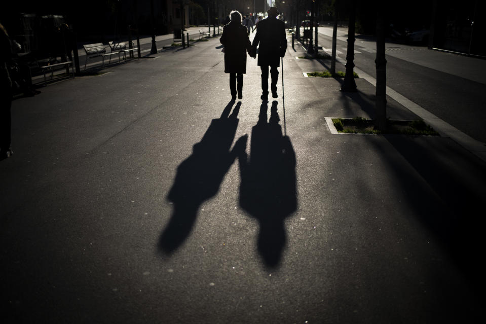 A couple walk along a boulevard in Barcelona, Spain, Sunday, Jan. 17, 2021. Scientists say it's still too early to predict the future of the coronavirus, but many doubt it will ever go away entirely. (AP Photo/Emilio Morenatti)