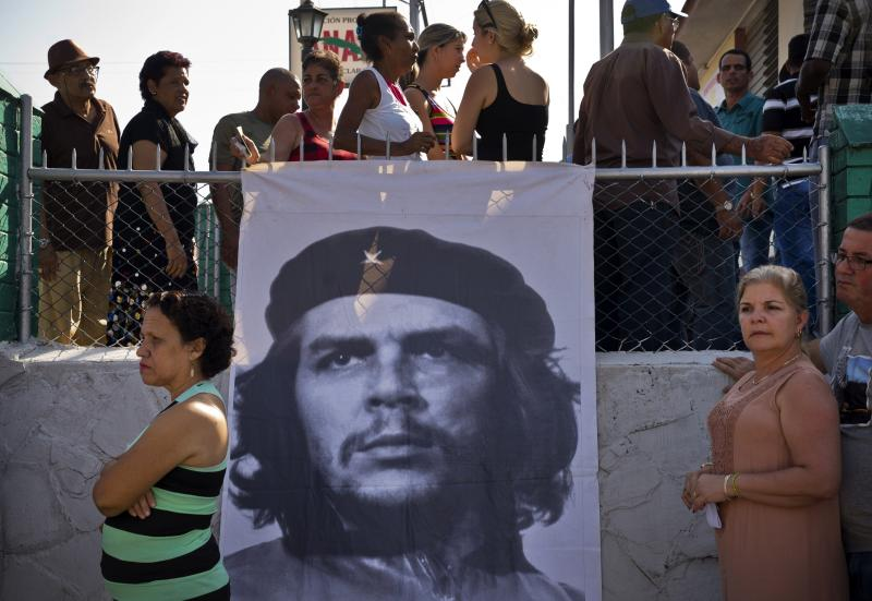 """People queue to vote in front of an image of Cuba's Argentine-born revolutionary hero Ernesto """"Che"""" Guevara at a voting center during elections for national and provincial representatives for the National Assembly in Santa Clara, Cuba, Sunday, March 11, 2018. (AP Photo/Ramon Espinosa)"""