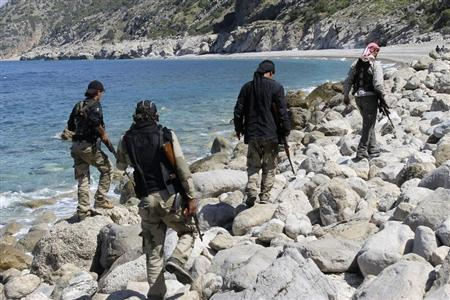Rebel fighters walk with their weapons at the beach in Latakia province near the town of Kasab