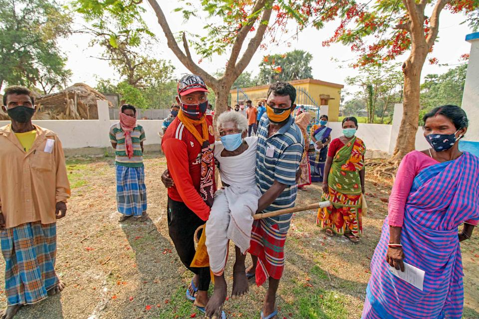 An elderly voter is carried to the polling booth to cast vote during the 8th phase of the Assembly elections at a polling station, Bandhlodanga in Birbhum district of West Bengal, Thursday, 29 April 2021.