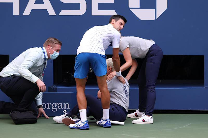 Novak Djokovic helps the line judge he hit with a tennis ball.