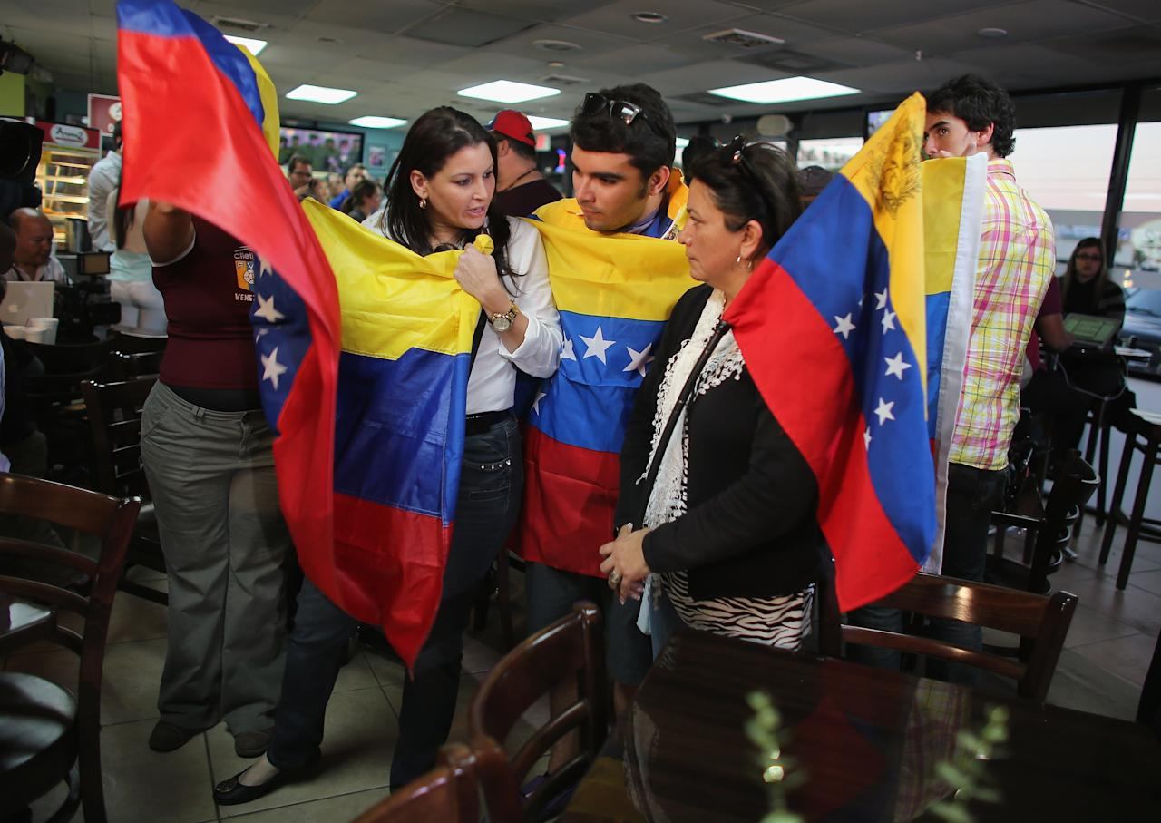 DORAL, FL - MARCH 05:  People hold Venezuelan flags as they listen to television sets reporting on the death of Venezuelan president Hugo Chavez, at El Arepazo 2  a restaurant in the heart of a neighborhood that has the largest concentration of Venezuelans in the U.S. on March 5, 2013 in Doral, Florida. The Venezuelan government announced today that Hugo Chavez lost his battle with cancer.  (Photo by Joe Raedle/Getty Images)
