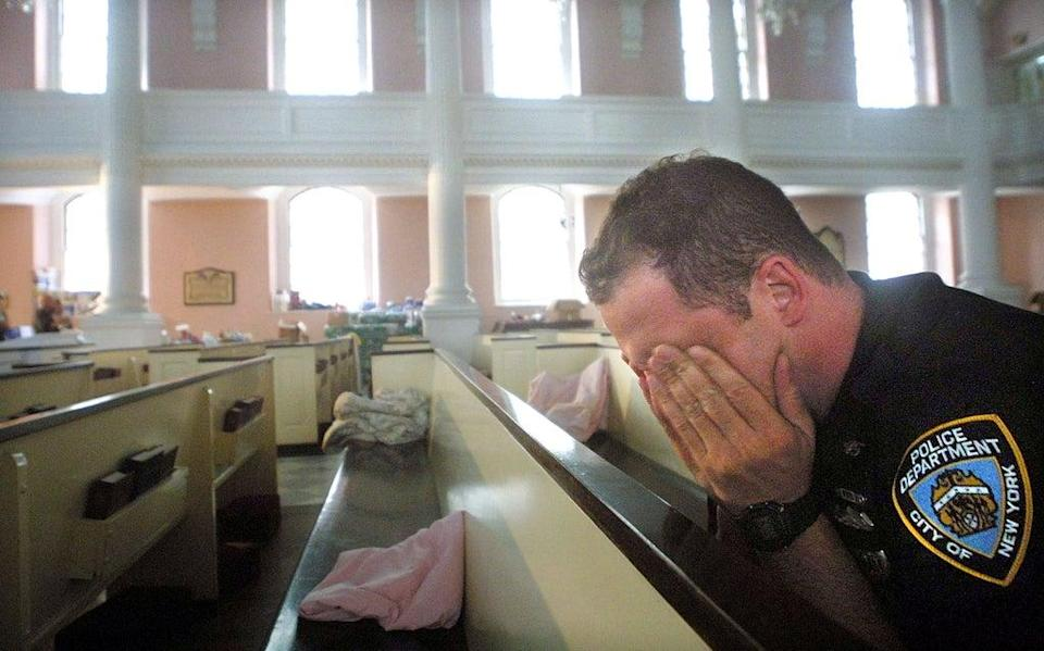 NYPD police officer Ken Radigan rubs his eyes after briefly sleeping in a pew at St Paul's Episcopal Chapel, near the site of the World Trade Center attack. The chapel served as a relief area for rescue workers (Getty)