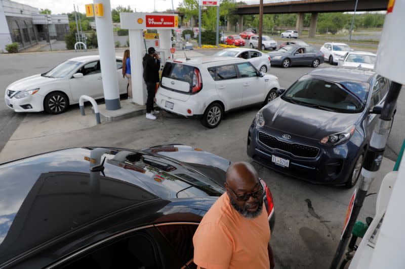 FILE PHOTO: A person fills their car with gas as people queue at a Shell gas station, after a cyberattack crippled the biggest fuel pipeline in the country, run by Colonial Pipeline, in Washington, D.C.