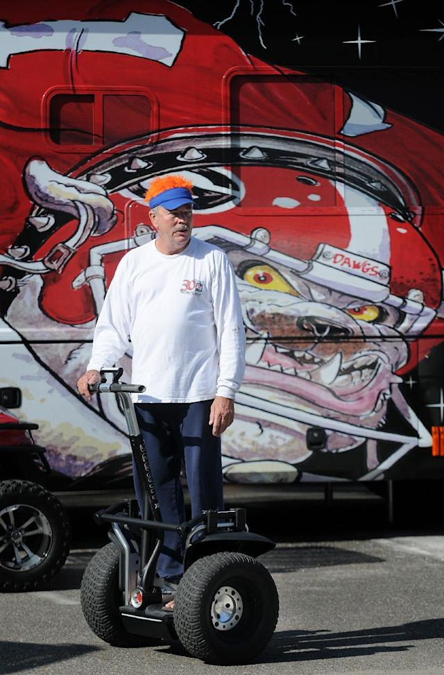 Frank Brunson, a Florida fan from Jacksonville, Fla., cruises past a Georgia Bulldog fan's motor coach in an RV parking lot, Wednesday, Oct. 30, 2013. Florida faces Georgia in an NCAA college football game Saturday in Jacksonville. (AP Photo/Florida Times-Union, Bruce Lipsky)