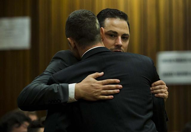Oscar Pistorius, front, gets a hug from his brother, Carl, back, in court in Pretoria, South Africa, Thursday, April 17, 2014. Pistorius is charged with the murder of his girlfriend, Reeva Steenkamp, on Valentines Day in 2013. (AP Photo/Alet Pretorius, Pool)