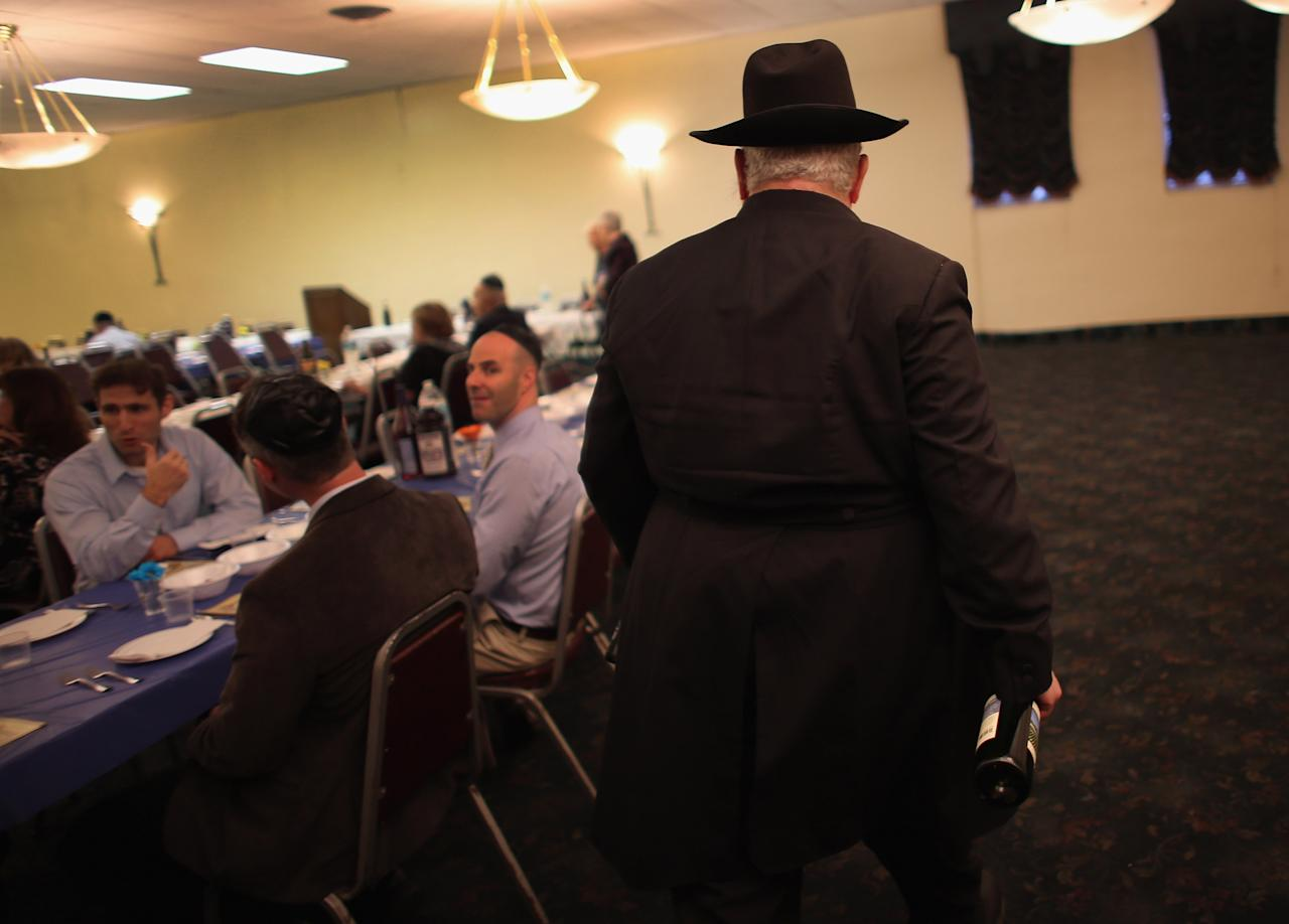 MIAMI BEACH, FL - MARCH 25:  Rabbi Efraim Katz brings wine to the tables for guests as he leads a community Passover Seder at Beth Israel synagogue  on March 25, 2013 in Miami Beach, Florida. The community Passover Seder that served around 150 people has been held for the past 30 years and is welcome to anyone in the community that wants to commemorate the emancipation of the Israelites from slavery in ancient Egypt.  (Photo by Joe Raedle/Getty Images)