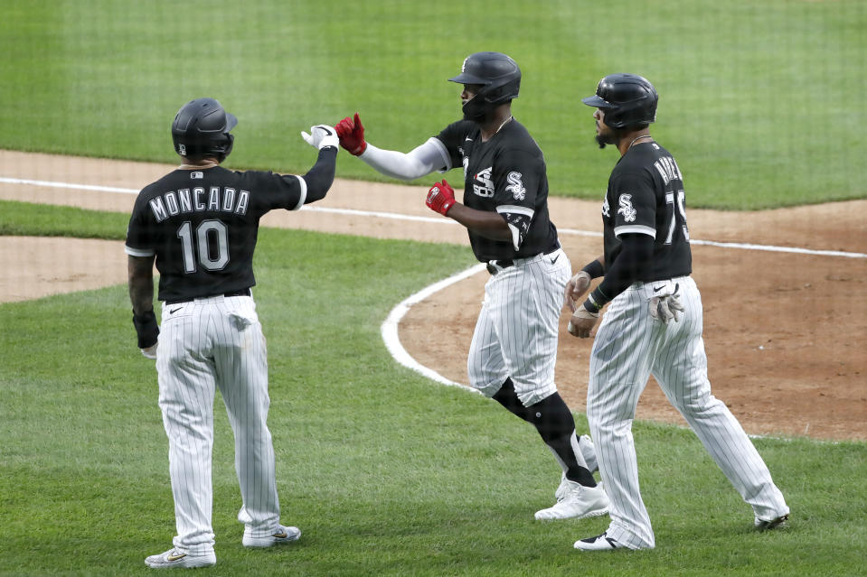 Chicago White Sox's Eloy Jimenez, center, celebrates his grand slam off Chicago Cubs starting pitcher Yu Darvish with Yoan Moncada and Jose Abreu during the first inning of a summer camp baseball game Monday, July 20, 2020, in Chicago. (AP Photo/Charles Rex Arbogast)