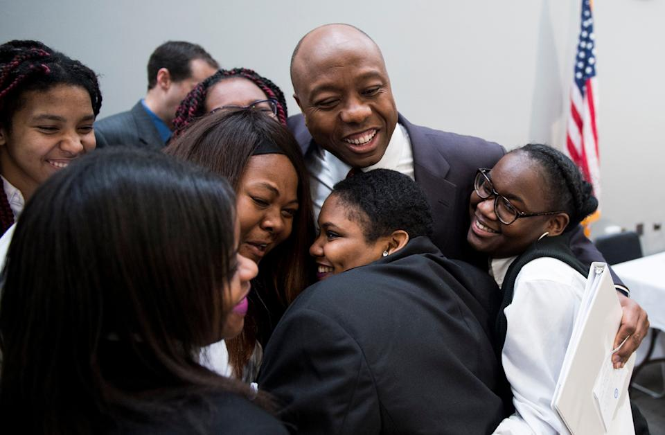 Sen. Tim Scott (R-S.C.) gives a group hug to students from the Richard Wright Public Charter School in Washington, D.C., during his National School Choice Forum in the Hart Senate Office Building on Feb. 9, 2015.