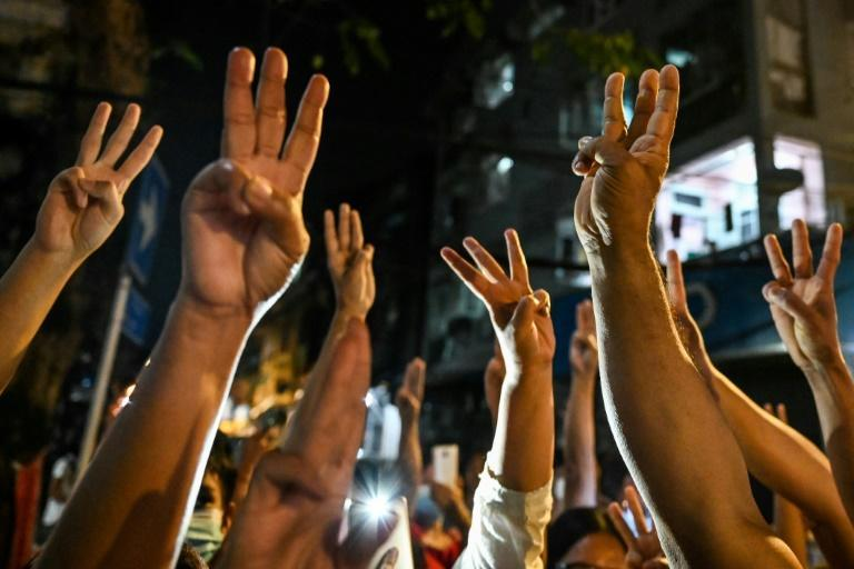 People give a three-finger salute after calls for protest went out on social media in Yangon on February 3, 2021, as Myanmar's ousted leader Aung San Suu Kyi was formally charged two days after she was detained in a military coup