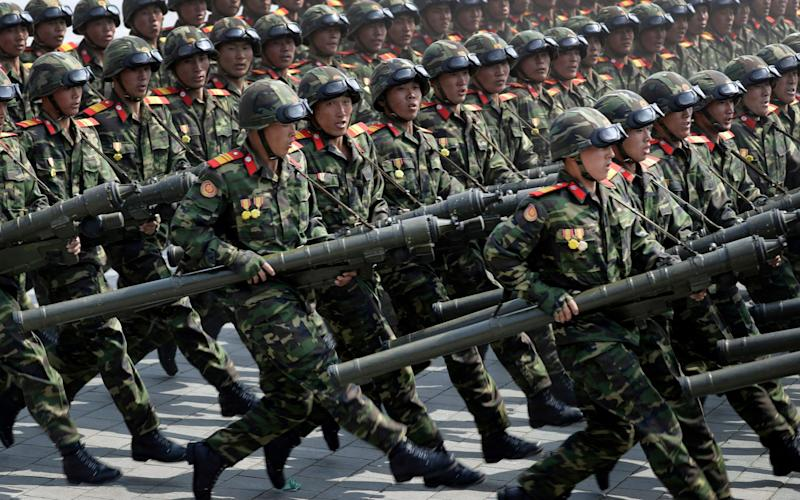 Soldiers carrying rockets march across Kim Il Sung Square during a military parade to celebrate the 105th birth anniversary of Kim Il Sung in Pyongyang - Credit: AP