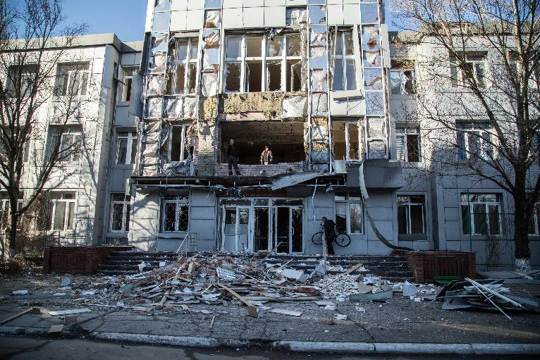 Ukrainians clear debris near a building destroyed after shelling in the eastern city of Avdiyivka, on February 23, 2015 (AFP Photo/Oleksandr Ratushniak)