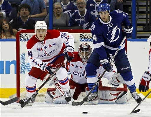 Washington Capitals goalie Michal Neuvirth, center, of the Czech Republic, looks for a shot between teammate John Carlson, left, and Tampa Bay Lightning's Brett Connolly during the first period of an NHL hockey game Monday, April 2, 2012, in Tampa, Fla. (AP Photo/Mike Carlson)