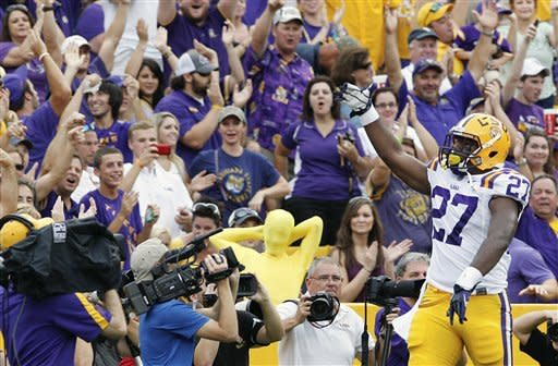 LSU running back Kenny Hilliard (27) salutes the fans after scoring a touchdown against North Texas during the first half of an NCAA college football game in Baton Rouge, La., Saturday, Sept. 1, 2012. (AP Photo/Bill Haber)