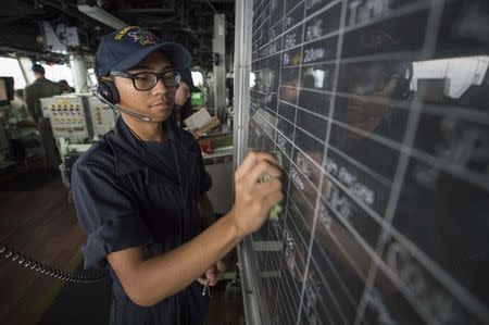 Seaman Kyren Mounsombath updates navigational information on the bridge of the amphibious assault ship USS Bonhomme Richard (LHD 6), flagship of the Bonhomme Richard Expeditionary Strike Group, in the South China Sea.    David Holmes/U.S. Navy/Handout via REUTERS