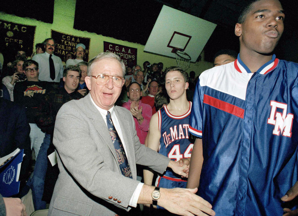 """FILE - In this Jan. 22, 1993, file photo, DeMatha High School basketball coach Morgan Wootten walks from the bench after his 1,000th victory, in Alexandria, Va. Next to Wootten are DeMatha players Tim Strachan (44) and Steve Napper, right. Morgan Wootten, a Hall of Fame basketball coach who built DeMatha High School into a national powerhouse and mentored several future NBA stars during a career that spanned parts of six decades, has died. He was 88. The school announced his death on Twitter, writing, The Wootten Family is saddened to share the news that their loving husband and father Morgan Wootten passed away"""" on Tuesday night, Jan. 21, 2020. (AP Photos/Ted Mathias, File)"""
