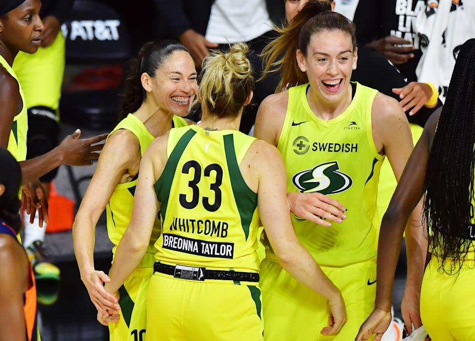 Sue Bird, Sami Whitcomb and Breanna Stewart in yellow Storm uniforms smile and celebrate.
