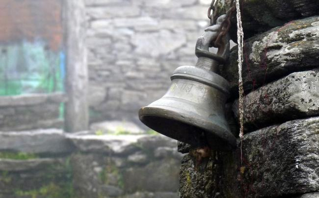 A bell rests against the stone wall of the temple.