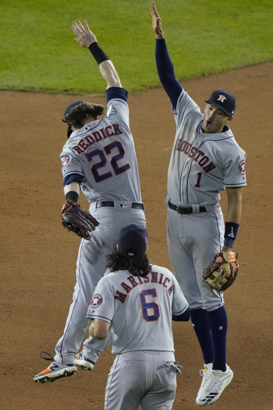 Houston Astros' Carlos Correa and Josh Reddick celebrate after Game 3 of the baseball World Series against the Washington Nationals Saturday, Oct. 26, 2019, in Washington. The Astros won 4-1. (AP Photo/Alex Brandon)