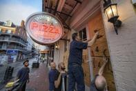 Michael Richard of Creole Cuisine Restaurant Concepts boards up Crescent City Pizza on Bourbon Street in the French Quarter before landfall of Hurricane Ida in New Orleans, Saturday, Aug. 28, 2021. Richard said the group is planning to board up and protect 34 restaurants owned by the company for the storm. (AP Photo/Matthew Hinton)