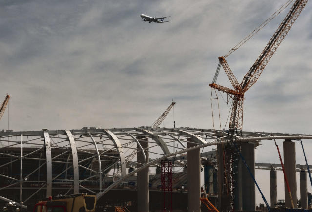 A commercial airliner makes a decent into Los Angeles International Airport over the new NFL Los Angeles Stadium under construction in Inglewood, Calif. on Monday April 15, 2019. Stadium officials hosted a tour for the media after the final piece of the canopy structure to hold the roof was completed. (AP Photo/Richard Vogel)