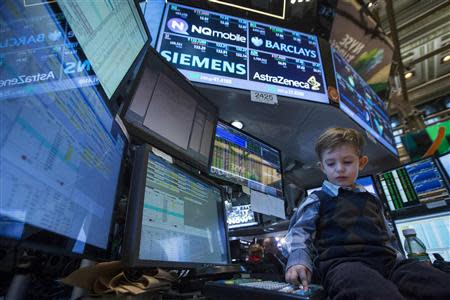 A young boy works at a trading post on the floor of the New York Stock Exchange November 29, 2013. REUTERS/Brendan McDermid