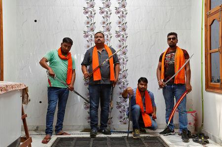 Hindu Yuva Vahini members pose inside the vigilante group's office in the city of Unnao, India, April 5, 2017. REUTERS/Cathal McNaughton