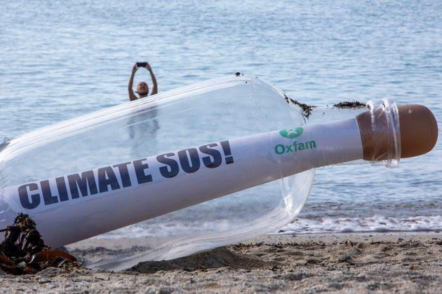 A giant message in a bottle has washed up on the beach from countries ravaged by climate change, on a beach on the 12th of June 2021 near Falmouth, Cornwall, United Kingdom. Oxfam is calling on the G7 countries to commit to cutting emissions further and faster and provide more finance to help the most vulnerable countries respond to the impacts of climate change.(photo by Andrew Aitchison/In Pictures via Getty Images) (Photo: Andrew Aitchison via Getty Images)