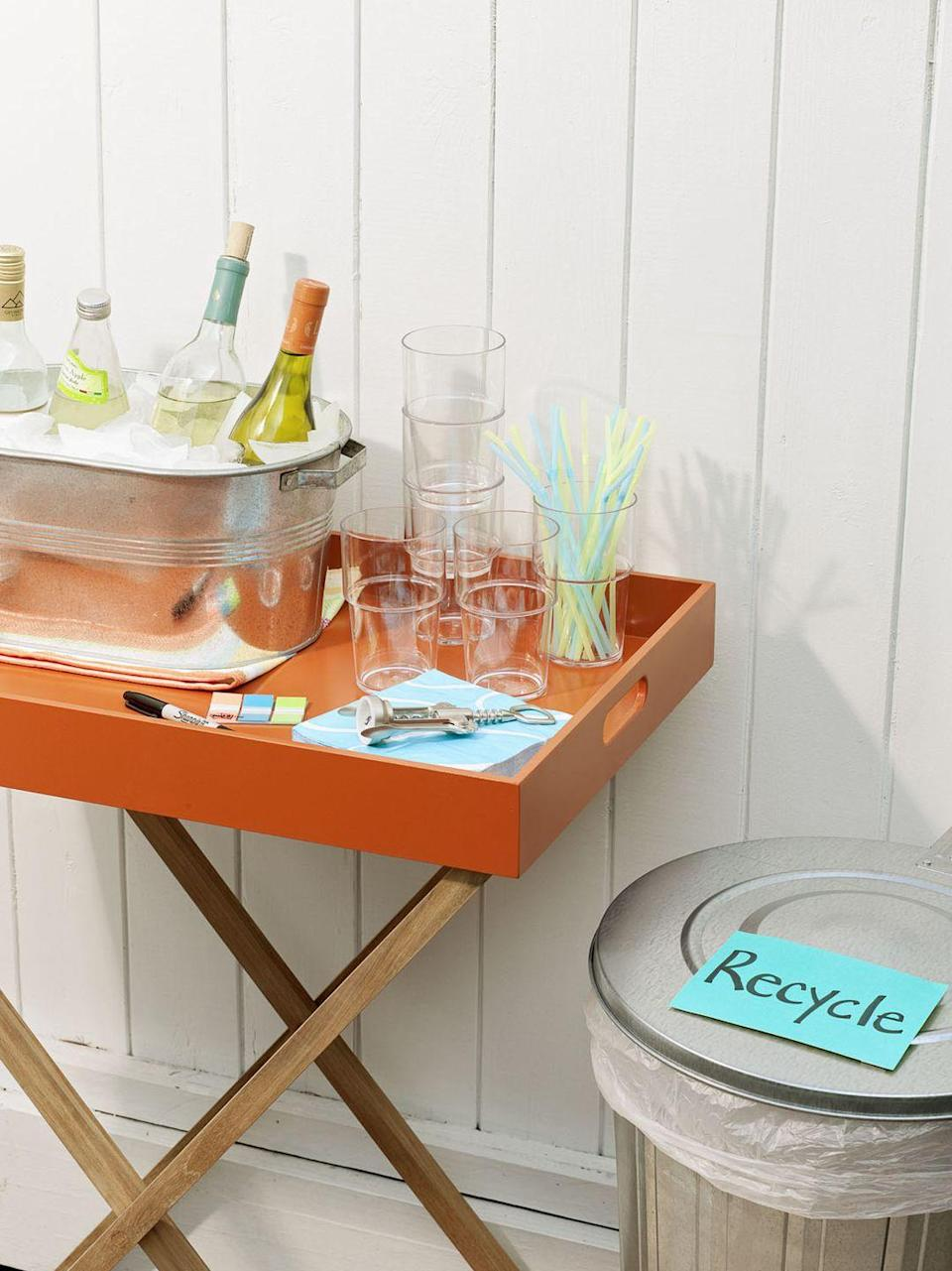 <p>A beverage station separate from the food lets guests mix drinks and mingle. Stock the bar with cups, straws (to double as stirrers) and plenty of ice — a large metal pail will keep bottles and cans frosty, but consider an insulated cooler for extra cubes. </p>