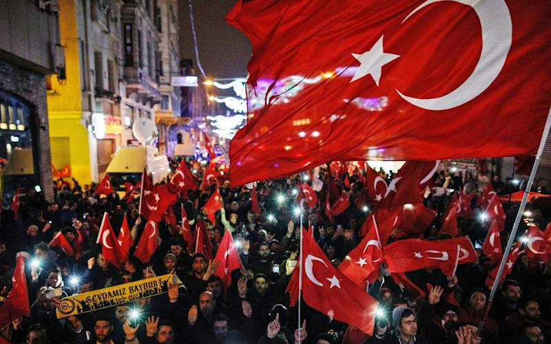 Protesters wave flags outside the Dutch consulate in central Istanbul's Istiklal Avenue