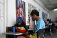 Marlon Carrillo (R) and his wife Yorgelis Materan have lunch in a church-run soup kitchen in Cucuta, Colombia December 15, 2017. REUTERS/Carlos Eduardo Ramirez
